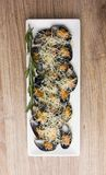 Fried mussels in the sink on a plate. Mussels in a sauce and grated Parmesan in a plate on a wooden table Royalty Free Stock Photos