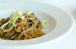 Fried noodle with abalone sauce and BBQ duck on white dish Stock Photos