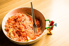 Fried noodle in a bowl of pink and a small robot. Royalty Free Stock Image