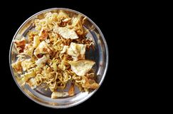 Fried noodle on a steel plate with fried eggs in black background with space for text.  royalty free stock image