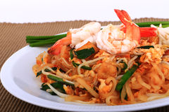 Fried noodle Thai style with prawns, Stir fry noodles with shrimp in padthai style on table. Front view isolate white , brown   ba Royalty Free Stock Photography