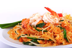 Fried noodle Thai style with prawns, Stir fry noodles with shrimp in padthai style on table. Front view isolate white , brown   ba Stock Image