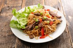 Fried noodles with beef. On wood background stock photography