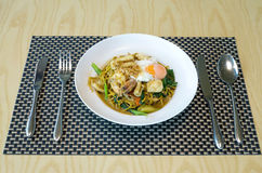 Fried noodles with sea food, vegetables and poached egg, thai fo Royalty Free Stock Photo