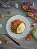 Fried noodles served with fried egg. Food flat lay concept. From top view on wood background stock images