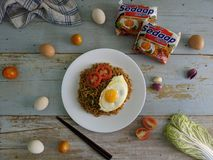 Fried noodles served with fried egg. Food flat lay concept. From top view on wood background royalty free stock images