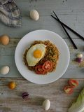 Fried noodles served with fried egg. Food flat lay concept. From top view on wood background royalty free stock photography
