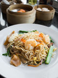 Fried noodles with shrimp and squid on white plate Stock Photos