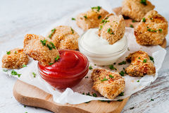 Fried nuggets dipped into two sauces Royalty Free Stock Images