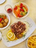 Fried octopus with lemon and spices, vegetables and french fries on white plate with glass of red wine stock photos