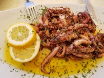 Fried octopus with lemon and spices on white plate with fork and knife stock photo