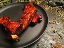 Fried oil ribs lie on a black frying pan. The frying pan stands on a dark wooden table among pieces of coal. Hay is lying around the frying pan Stock Photo