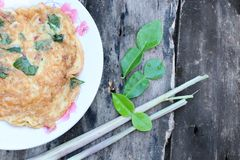 Fried omelette, herbs, add basil, onion, red pepper, lemongrass, kaffir lime leaves in a red dish, vintage wooden background. Thai food menu fried omelette herbs stock photos
