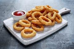 Fried Onion Rings avec le ketchup sur la planche à découper blanche Images libres de droits