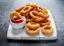 Fried Onion Rings con la salsa de tomate en la tabla de cortar blanca Imagenes de archivo