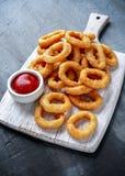Fried Onion Rings con la salsa de tomate en la tabla de cortar blanca Imagen de archivo