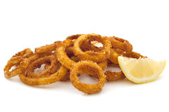 Fried Onion Rings Over White. Pile of fried onion rings with a lemon wedge, over white background royalty free stock image