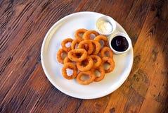 Fried Onion Rings y salsas en la tabla de madera Fotografía de archivo libre de regalías
