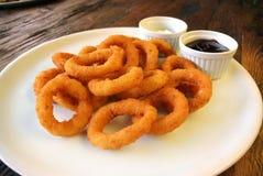 Fried Onion Rings y salsas en la tabla de madera Imagenes de archivo