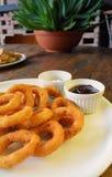 Fried Onion Rings y salsas en la tabla de madera Fotografía de archivo