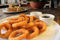 Fried Onion Rings y salsas en la tabla de madera Imagen de archivo libre de regalías