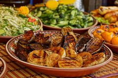 Fried onions and fried eggplants in a plate on a table with other dishes. Baked vegetables and salads in plates on the table royalty free stock images