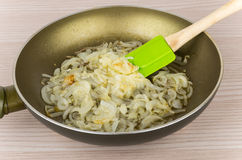 Fried onions in oil in pan on table Royalty Free Stock Photography