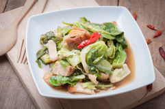 Fried Oyster sauce vegetables sect with crispy pork on wood floo. Rs, The national cuisine of Thailand Stock Photos