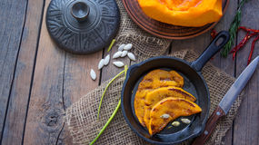 Fried in a pan and grill the slices of juicy orange pumpkin with spices country - style in low key Stock Images