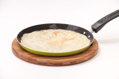 The fried pancake in a frying pan over white background Royalty Free Stock Images