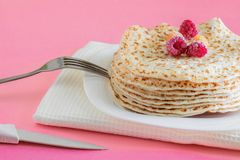Fried pancakes close-up on a white plate, pancakes with raspberries, dessert on a pink background, place for text stock images