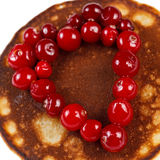 Fried pancakes with cranberries in heart shape isolated on white Stock Photo
