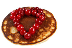 Fried pancakes with cranberries in heart shape isolated on white Royalty Free Stock Images