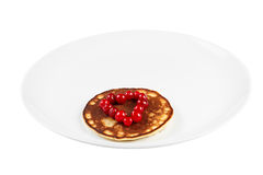 Fried pancakes with cranberry heart shaped with honey on a plate Stock Photos