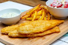 Fried pangasius basa fish fillet swai river cobbler bocourti with french fries side view sour cream dip feta salad stock image