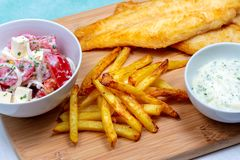 Fried pangasius basa fish fillet swai river cobbler bocourti with french fries sour cream dip feta salad close up. On turquoise napkin in background stock images