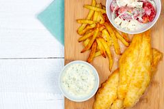 Fried pangasius basa fish fillet swai river cobbler bocourti with french fries top view sour cream dip feta salad royalty free stock image