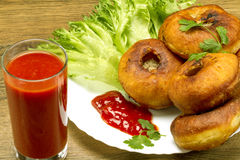 Fried patty on a plate with greens and tomato juice. Fried patty on a plate with tomato juice and ketchup on salad Royalty Free Stock Images