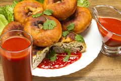 Fried patty on a plate with greens and tomato juice. Fried patty on a plate with tomato juice and ketchup on salad Royalty Free Stock Image