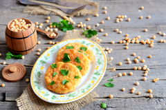 Fried pea cutlets on a plate. Healthy vegetarian cutlets cooked from yellow dried peas and decorated with fresh parsley Royalty Free Stock Photo