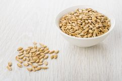 Fried peeled sunflower seeds in bowl and on table stock photo