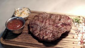 Fried piece of meat served on wooden tray. Action. Close-up of juicy piece of steak cooked by professional chef and. Served on tray on isolated background stock video