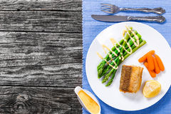 Fried piece of sea fish served with green asparagus Stock Photos