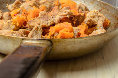 Fried pieces of meat and pumpkin in a pan Stock Images