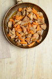 Fried pieces of meat and pumpkin in a pan Stock Photos