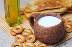 Fried pies, cheese, sunflower oil, milk and bagels on a plate cl Royalty Free Stock Image
