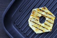 Fried pineapple on the grill. Cooking fish burger. Stock Images