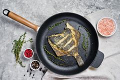 Fried plaice in a pan. Gray background, top view. stock image