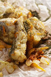 Fried pollock fillet closeup. Pollock fish fillet fried with carrots and onions on a parchment closeup stock photo