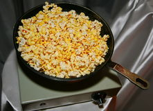 Fried popcorn in an old cast iron skillet on the light green vintage electric tile on the background of gray-silver fabric draping Stock Photo